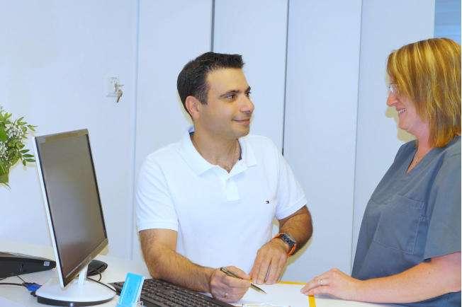 Zahnarzt Maximilian Hagen und eine Angestellte im Gespräch